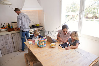 Dad cooking and mum with kids at kitchen table, high angle
