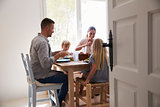 Family eating at table in sunlit room