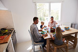 Family sitting down to eat lunch at kitchen table