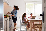 Mum cooking while kids work at kitchen table, from doorway