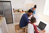 Parents helping kids with homework in kitchen, elevated view
