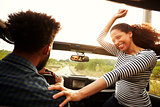 Man driving with excited woman passenger in front of car
