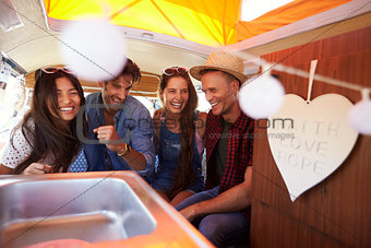 Four friends laughing in the back of a camper van