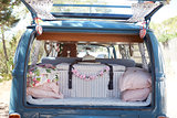 Open back of a retro camper van, with luggage and cushions