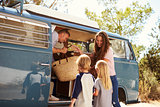 Family packing up their camper van for a road trip vacation
