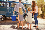 Family preparing their camper van for a road trip, back view
