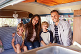 Smiling family portrait inside camper van