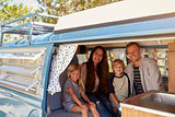 Family inside vintage camper van, seen through open door