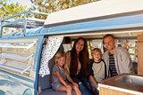 Family inside vintage camper van, seen through open door