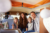 Smiling family sitting in the back of vintage camper van