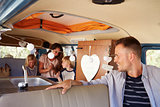 Dad in driving seat of camper van looks back at his family