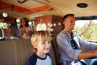 Dad driving family in a camper van, with son up front