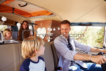 Dad driving family in a camper van, looking at his son
