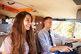 Happy couple driving a camper van on a road trip vacation