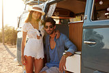 Couple relaxing in the doorway of camper van look to camera