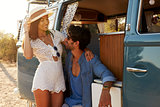 Couple relaxing in the doorway of their camper van
