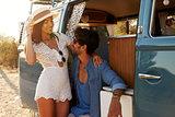 Couple relaxing in the doorway of their camper van