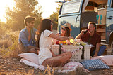 Friends on a road trip  having a picnic beside a camper van