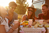 Friends having a picnic beside a camper van, close up