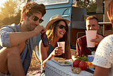 Friends on a road trip having a picnic beside a camper van