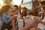 Friends enjoying a picnic beside their camper van