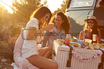 Three female friends talking at a picnic by their camper van