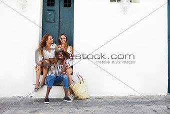 Three female friends sitting in a doorway, Ibiza