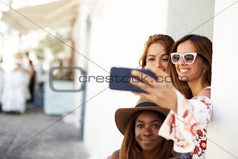 Three female friends taking a selfie in the street, Ibiza