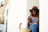 Young woman on holiday sitting on steps looking at phone