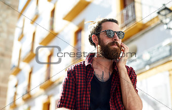Bearded young man in sunglasses using phone, Ibiza, Spain