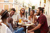 Friends on vacation laughing outside a cafe in Ibiza