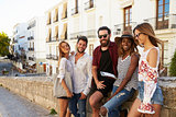Five friends on vacation in Ibiza town looking to camera
