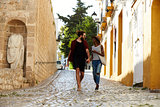 Couple on holiday walking in Ibiza streets talking