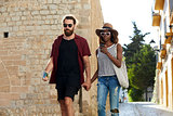 Couple on holiday walk, looking at phone, Ibiza, Spain
