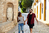 Happy couple on holiday hold hands walking in Ibiza, Spain
