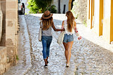 Two female friends on holiday walking arm in arm, back view