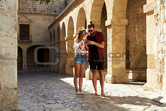 A couple sightseeing in Ibiza using a phone for guidance