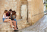 Friends sit on a wall looking at photos on a camera, Ibiza