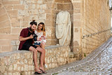 Couple sitting on wall looking at photos on a camera, Ibiza
