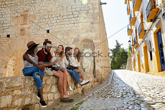 Five friends on holiday sitting on a wall in Ibiza