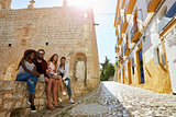 Friends on holiday in Ibiza sit on a wall looking to camera
