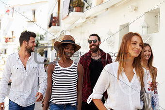 Five friends on vacation walking through town, Ibiza, Spain