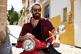 Bearded young man sitting on motor scooter, Ibiza, Spain
