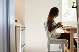 Young woman sitting in kitchen reading and drinking coffee