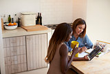 Two friends sitting in kitchen, using tablet and reading