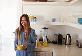 Young woman standing in kitchen holding cup, waist up, Ibiza