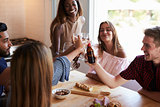 Five happy friends make a toast at a kitchen dinner party