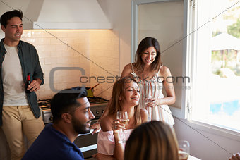 Five friends hanging out together drinking in the kitchen