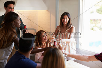 Five friends socialising in the kitchen making a toast