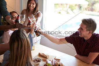 Five friends make a toast at a dinner party in the kitchen